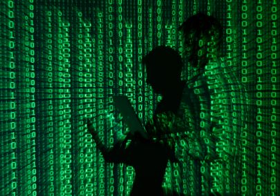 An illustration picture shows a projection of binary code on a man holding a laptop computer, in an office in Warsaw June 24, 2013. REUTERS/Kacper Pempel (POLAND - Tags: BUSINESS TELECOMS)